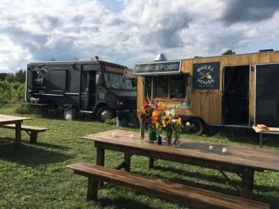 Farm tables and food trucks at a wedding