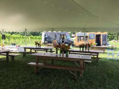 farm tables and food trucks at a wedding